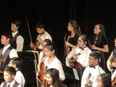 Students standing with strings instruments
